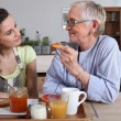 Stock Photo: Grandmother and granddaughter having breakfast