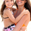 Mother and daughter at the beach together - Stock Photo