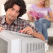 Husband fixing the TV. - Stock Photo