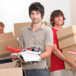 Stock Photo: House mates carrying boxes