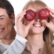Young man holding red apples before girfriend's eyes — Stock Photo #9165752