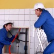 Apprentice passing red cable up behind a tiled wall — Stock Photo #9166592
