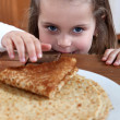 Little girl with stack of pancakes — Stock Photo #9167454