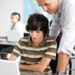 Stock Photo: Teacher helping male pupil