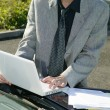Stock Photo: Mresting his laptop on car bonnet