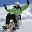 Woman sat on sledge - ストック写真