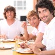 Stock Photo: Three young men having lunch