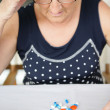 An elderly woman looking at her medication — Stock Photo