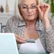 Older woman using her credit card online — Stock Photo