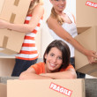 Three young women moving cardboard packing boxes marked fragile — Stock Photo #9169045