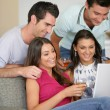 Two couples at home laughing at a laptop — Stock Photo