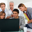 Royalty-Free Stock Photo: A bunch of gathered behind a laptop