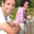 Couple leaning against a wooden barrier — Stock Photo