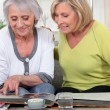 Older women looking at a photo album — Stock Photo