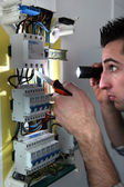 Electrician examining a fusebox with a torch — Stockfoto
