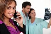 Geschäftsfrau auf telefon und betreuer beobachten röntgen — Stockfoto
