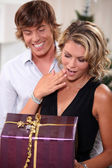 Young man giving his girlfriend a Christmas present — Stock Photo