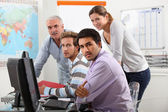 Group of casually dressed working round a computer — Stock Photo