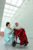 Young brunette nurse and elderly dame in wheel chair in hospital — Stock Photo