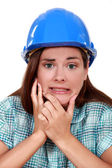 Indecisive woman in a hardhat — Stock Photo