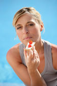 Woman eating cracker based snack by the pool — Stock Photo