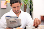 Man having a leisurely breakfast while reading the paper — Stock Photo