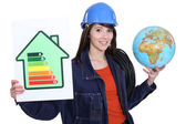 Woman holding an energy-saving drawing and a globe and wires — Stock Photo