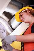 Tradeswoman reading a blueprint — Stock Photo