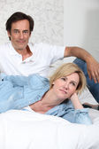 Fully clothed couple lying on a bed watching television — Stock Photo