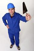 Laborer showing trowel, studio shot — Stock Photo