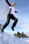 Woman jumping onto a pile of snow — Stock Photo