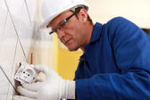 Electrical engineer fixing socket — Stock Photo