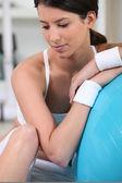 Ung kvinna vilar på en övning boll — Stockfoto
