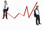 Reduced size man in coat and tie on either side of red arrow against graph — Stock Photo