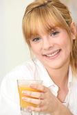Blond woman drinking orange juice — Stock Photo