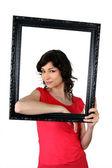Mujer se mantiene dentro de un marco de imagen — Foto de Stock