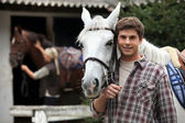 A young man with a horse. — Stock Photo