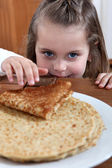 Little girl with stack of pancakes — Stock Photo