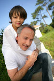 Little boy sat on his father's shoulders — Stock Photo