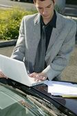 Man resting his laptop on car bonnet — Stock Photo
