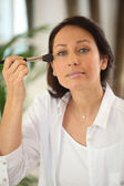 Thirty years old woman applying blush — Stock Photo