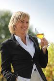 Kobieta w czarnej kurtki picie kieliszek białego wina w winnicy — Zdjęcie stockowe