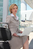 Businesswoman on laptop outside airport — Stock Photo
