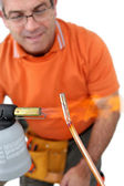 Plumber soldering pipe — Stock Photo