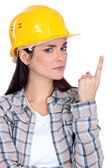 Portrait of young craftswomen looking concerned pointing upwards — Stock Photo