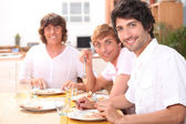 Three young men having lunch — Stock Photo