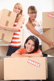 Three young women moving cardboard packing boxes marked fragile — Stock Photo