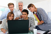 A bunch of gathered behind a laptop — Stock Photo