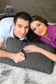 A couple lying on a carpet — Stock Photo