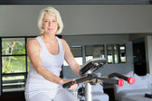 Mature woman using an exercise bike at home — Stock Photo
